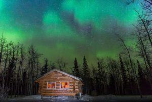 beleuchtete Bella Luna Blockhuette mit Nordlichthimmel fotografiert im Yukon in Kanada Nordamerika Reisen und Fotografieren