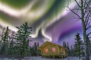 Blockhaus Unterkunft in der Yukon Wildnis mit farbigem Nordlichter Himmel. Aurora Borealis Cabin Nachtfotografie