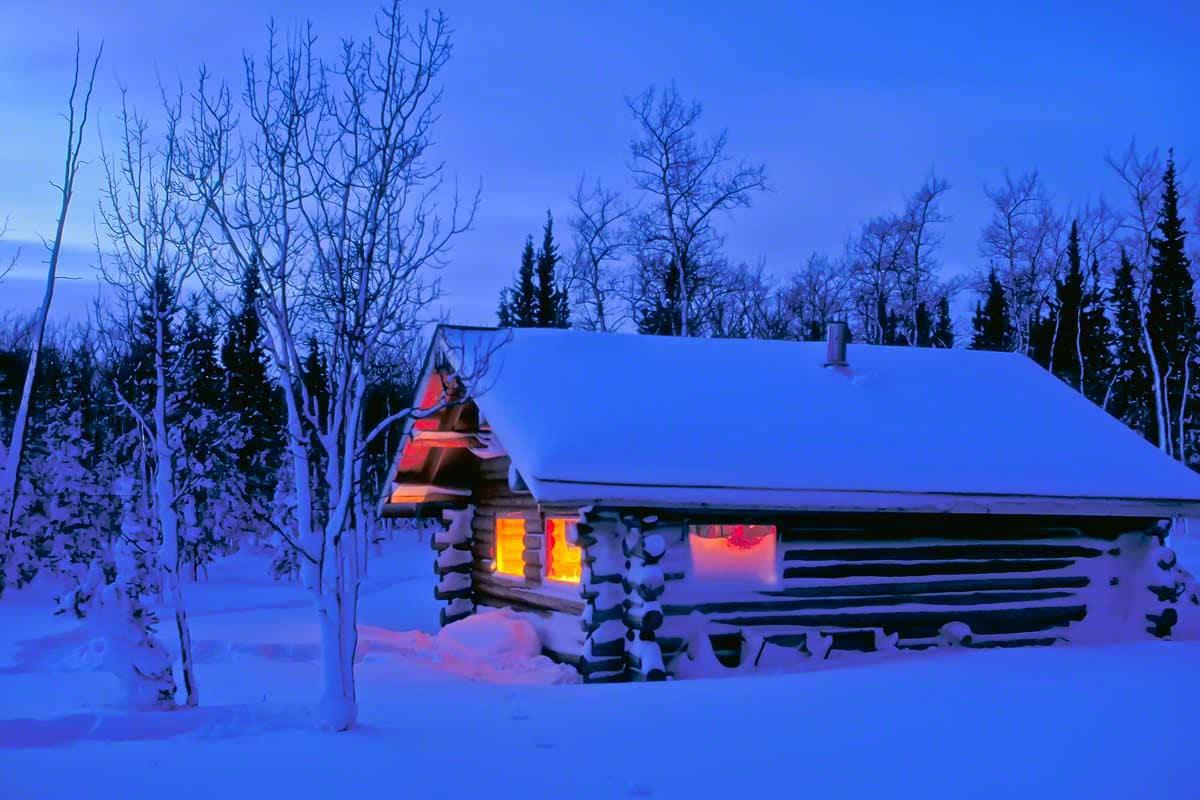 verschneites Blockhaus Hütte in der Wildnis vom Yukon Trapper. Leben im Winter Abenteuer Alaska Einsamkeit Haus mieten in Kanada