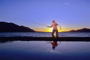 Fliegen Fischen Angeln im Gegenlicht vom Sonnenuntergang am Kluane Lake im Yukon Urlaub mit dem Kanu unterwegs paddeln