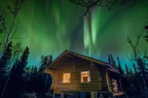 Neue Blockhütte am Kluane National Park fotografiert unter Nordlichterhimmel. Beleuchtete gemütliche Cabin im Yukon