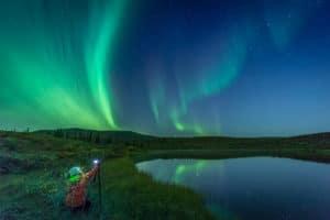 Nordlichter fotografieren in einer Polarnacht am Dempster Highway mit Spiegelbild im See. Fotorundreisen Arktis mit Profifotograf.