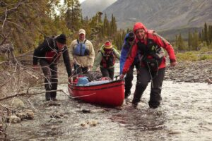 Liard River Kanutouren im Yukon unterwegs paddeln und Wildnis pur erleben Gruppe zieht Kanu durch untiefen Bachlauf