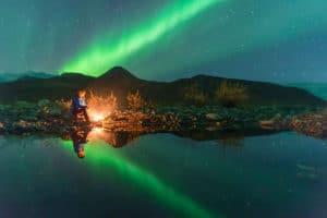 Aurora Borealis Spiegelbild Nordlichter am Lagerfeuer am See im Yukon Dempster Highway auf Fotorundreise zum Polarkreis