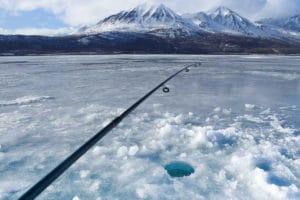 Eis angeln im Winter fischen auf gefrorenem See am Kluane National Park gebortes Eisloch mit Angel Winterreisen Kanada