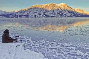 Kluane Lake Yukon spektakuläre Landschaftsfotografie. Ein Hobbyfotograf macht ein Bild am gefrorenen See Reisen Kanada mit Berufsfotograf auf Touren