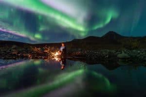 Indian Summer Tourengast unter Nordlichter fotografiert mit Lagerfeuer und Spiegelbild im See Arktis Reisen Norden