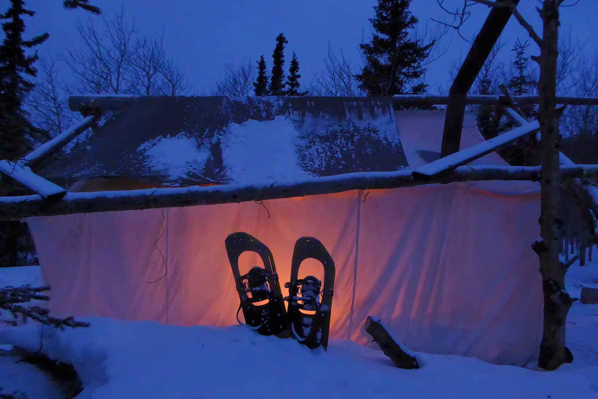 Trapperzelt beleuchtet in der blauer Stunde mit Schneeschuhen im Vordergrund. Unterkunft auf Schneeschuhreisen unterwegs im Norden.