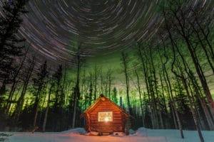 Einsame Blockhütte im kanadischen Wald mit Nordlichter Himmel. Fotografie Langzeit- Nachtaufnahme beleuchtete Cabin